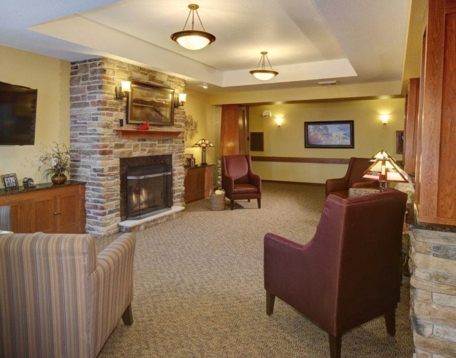 A Heritage Elm Grove community space with comfortable chairs and a fireplace.