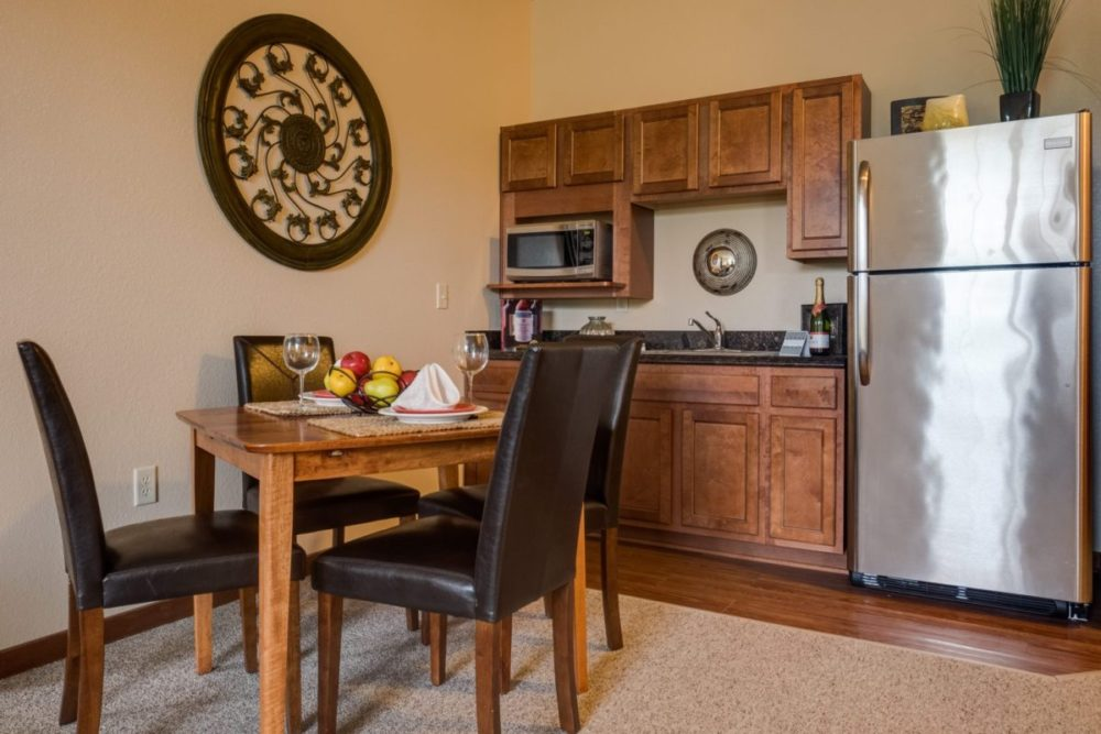 A Heritage Elm Grove apartment kitchen with a fridge and dinning table for four.
