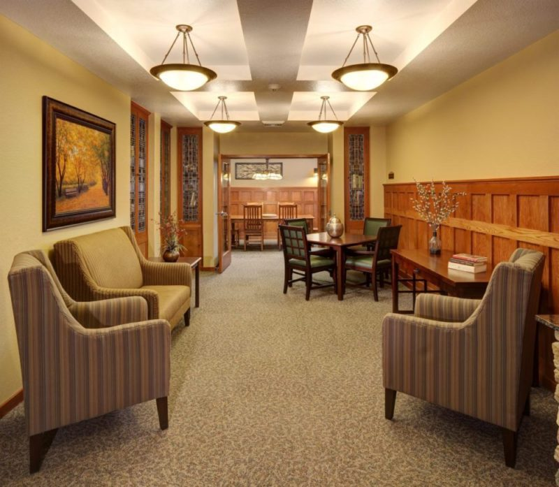 The sitting area with comfortable chairs and tables in Heritage Elm Grove's library