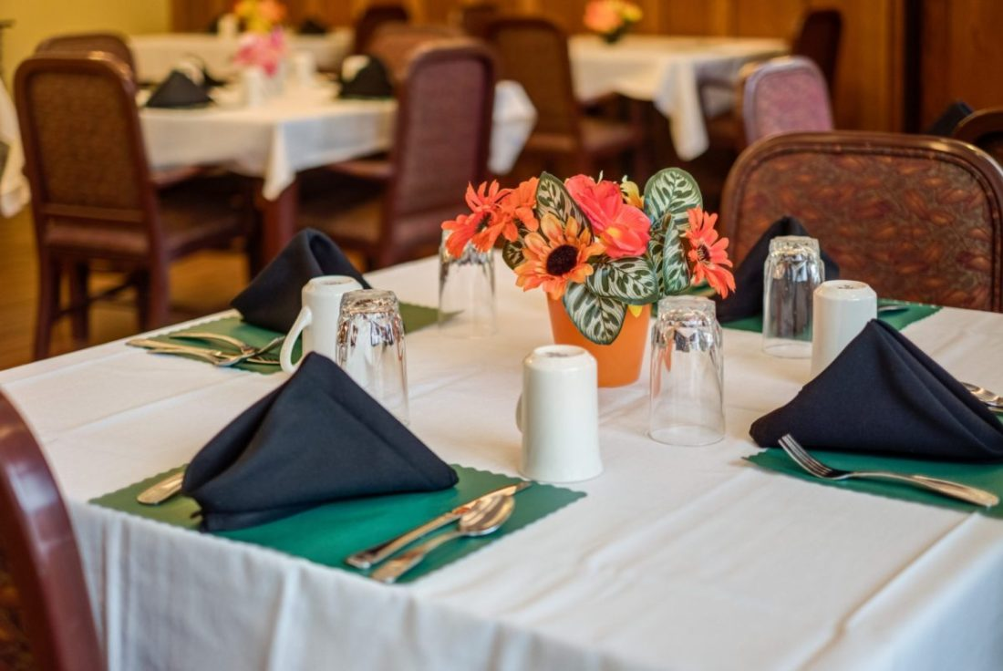 A dining room table for four with flowers at Heritage Court Eau Claire.