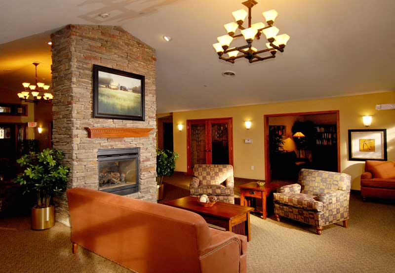 Heritage Court Eau Claire's entry are with a fireplace and cozy lounge area.