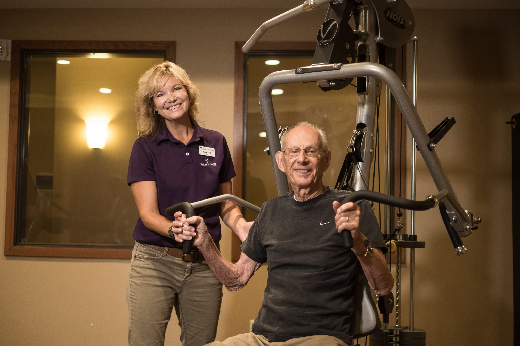 senior man working out with a physical therapist