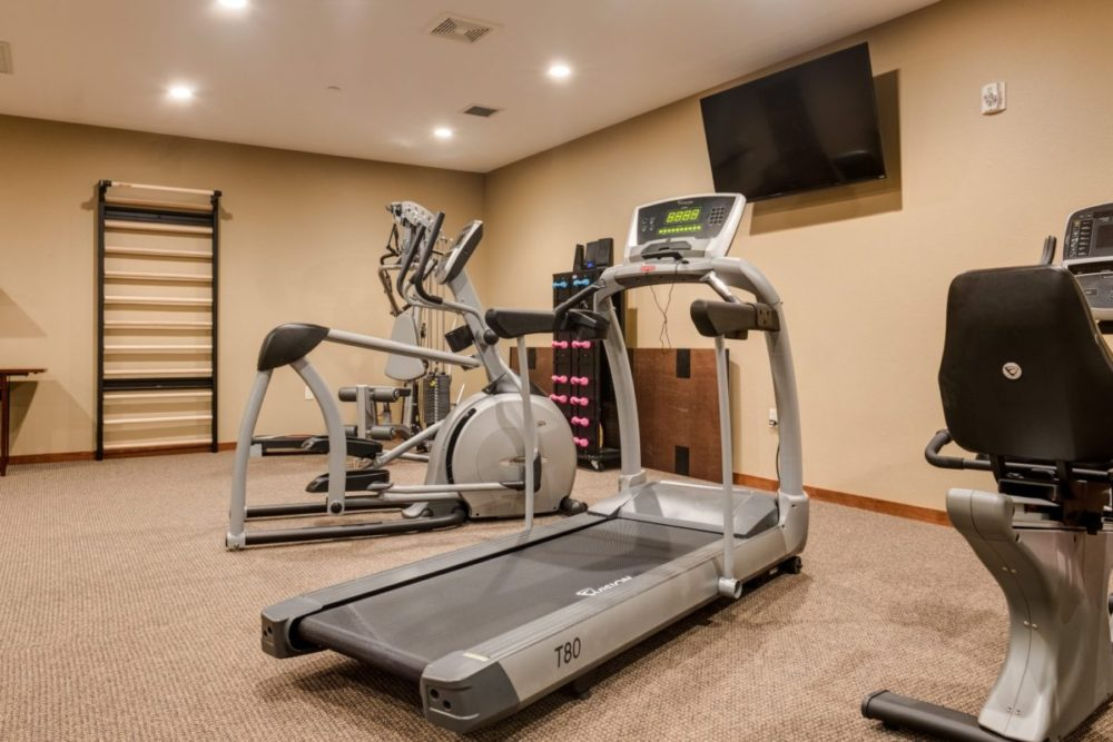 A treadmill, elliptical, and weights in the Heritage Lake Country gym.