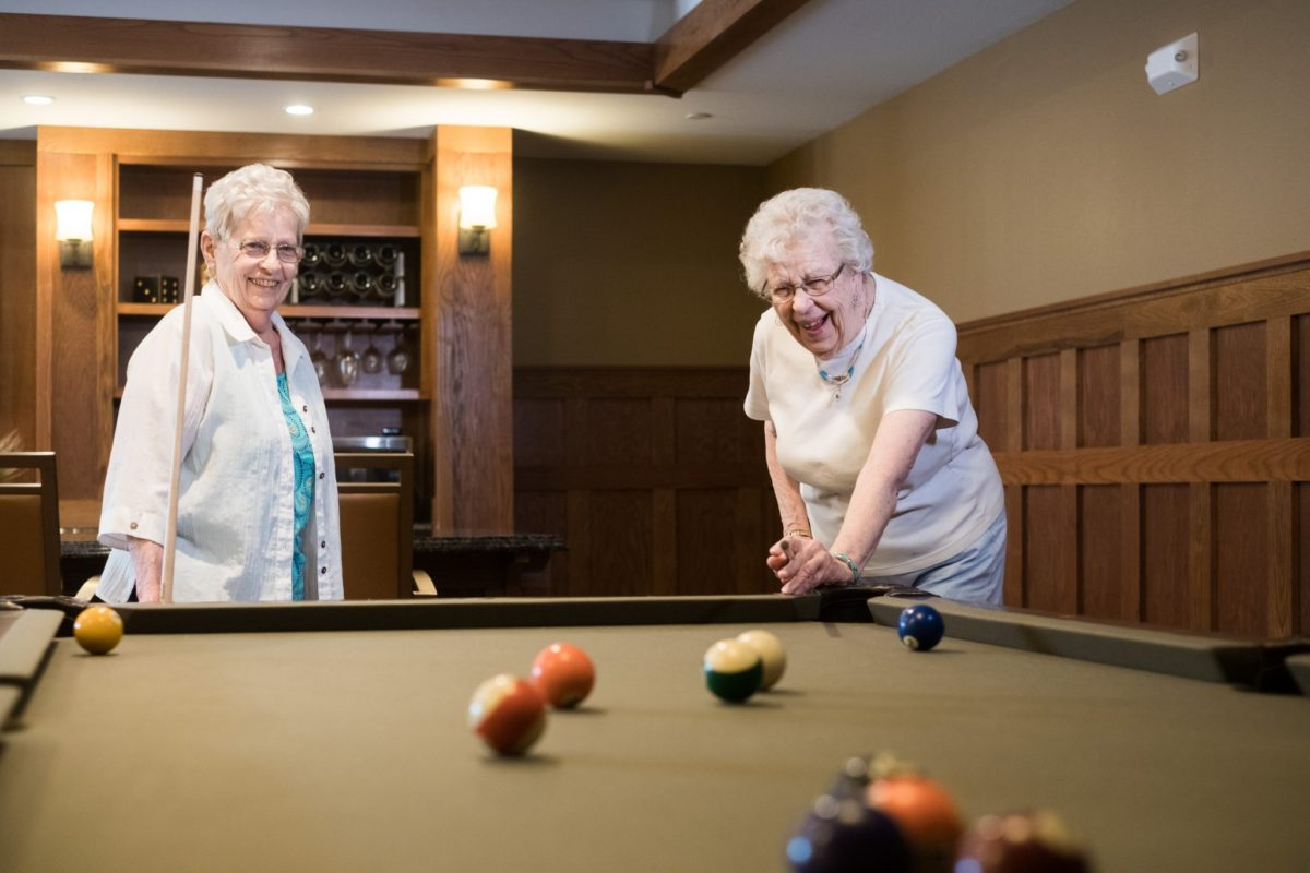Two senior ladies enjoy a game of billiards in the Heritage Lake Country's pub area.