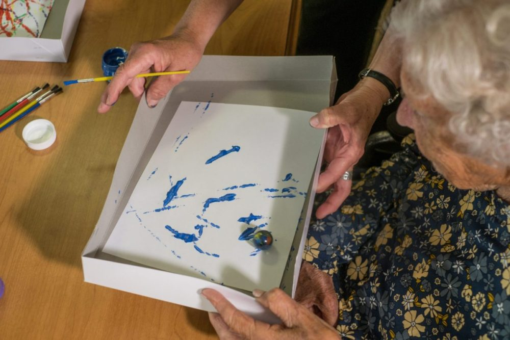 Female resident enjoys art with our staff as part of our activities option at Heritage Lexington.