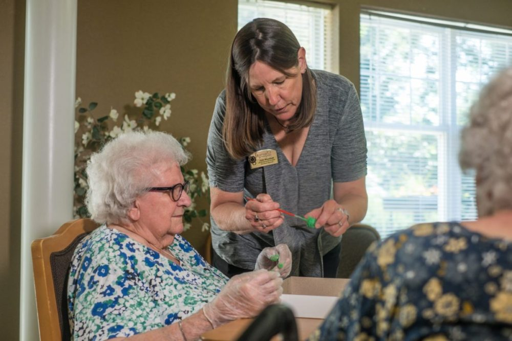 Lexington Heritage team member aids senior woman during our arts and craft focused activity.