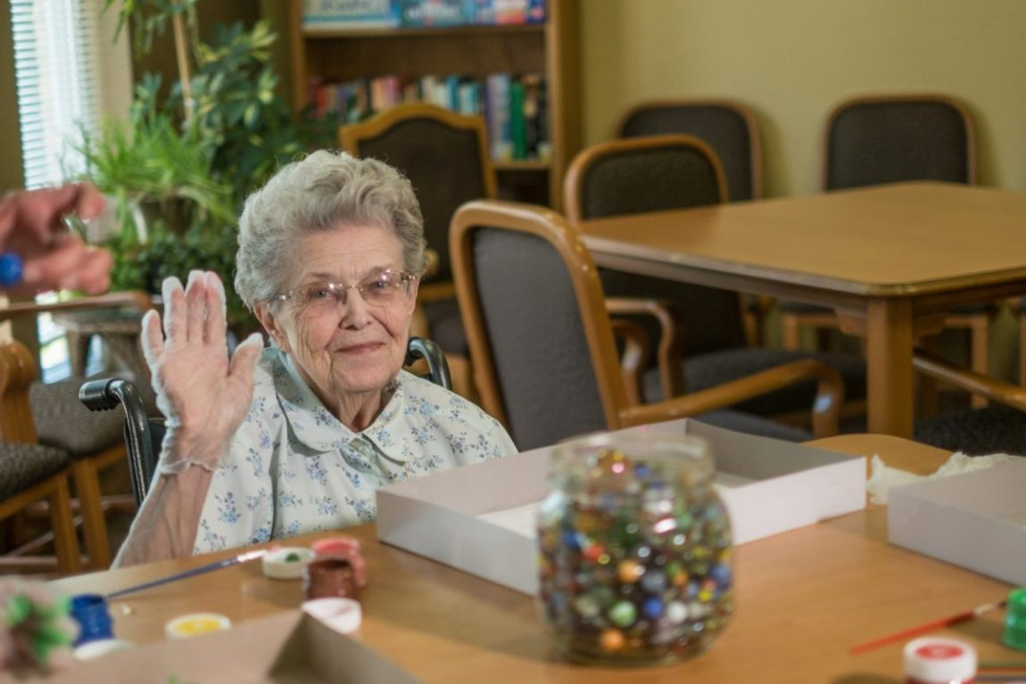 A senior woman waves during an art focused activity at Heritage Lexington.