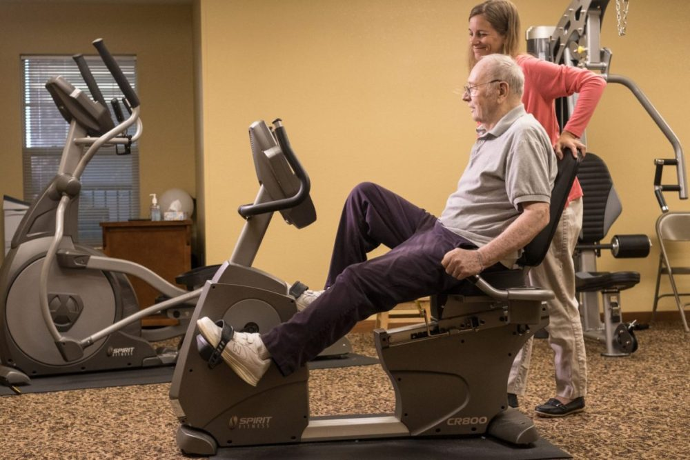 A senior works with a staff member to use an exercise bike.