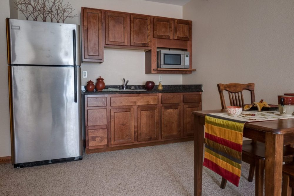 A kitchenette and dining area in a Heritage Middleton assisted living apartment.
