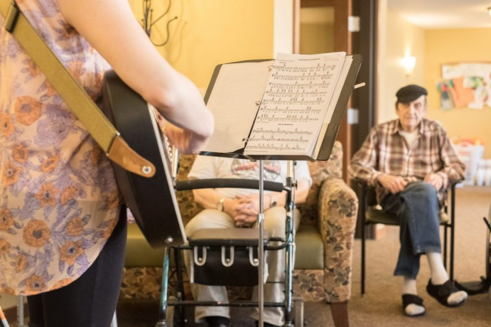 A young woman plays guitar for seniors during music therapy.