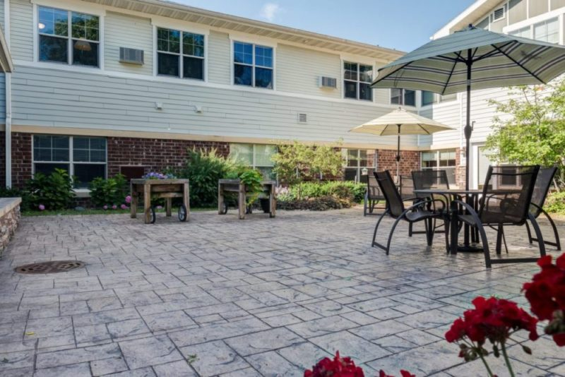 Outside patio for residents to enjoy with patio chairs, tables, and umbrellas at Heritage Monona.