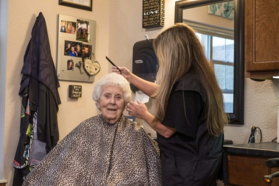 Senior woman enjoys the salon at Heritage Monona and gets her hair styled by female stylist.