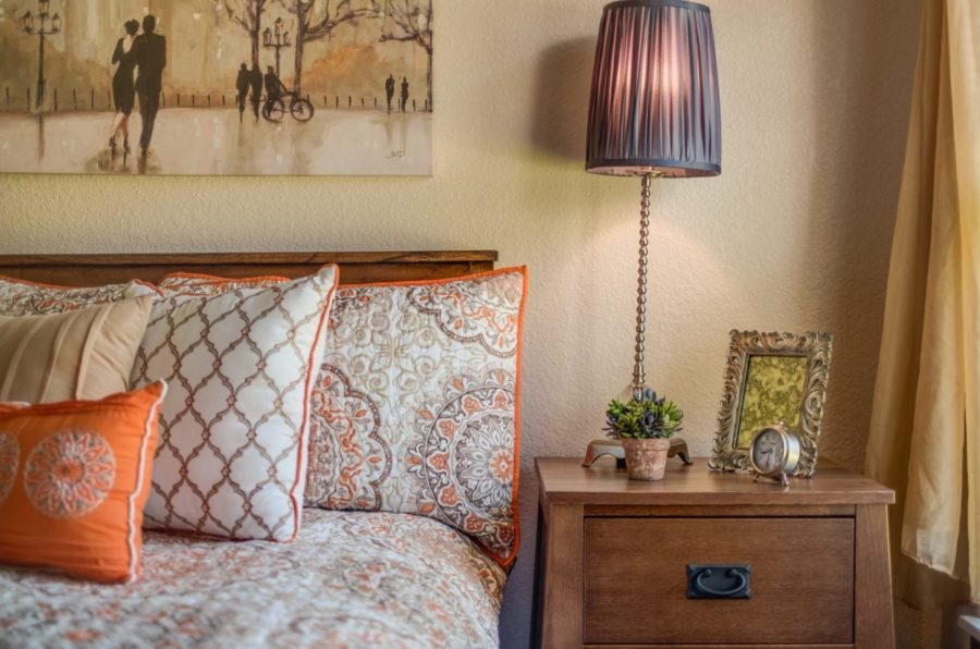 Apartment suite with bed, nightstand, and lamp at Heritage Monona.