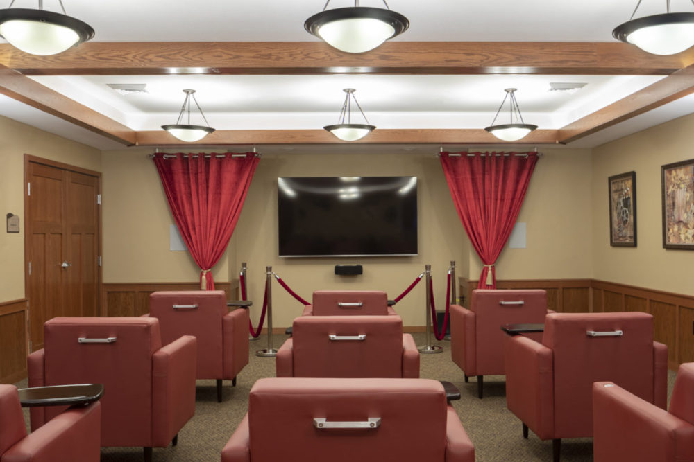 Heritage Muskeogo's theater room with comfortable red lounge chairs.