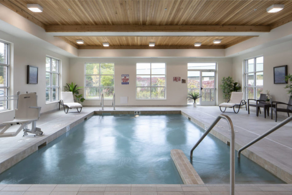 A warm-water indoor pool with a chair lift and lounge chairs.