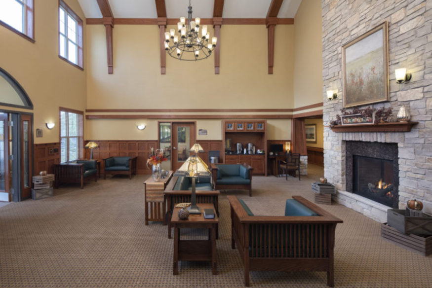 The open lounge area at Heritage Muskego with fireplace, couches, coffee bar, and chairs.