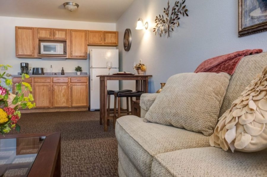 The kitchenette, small table, and sofa in an independent living apartment at Heritage at Deer Creek.