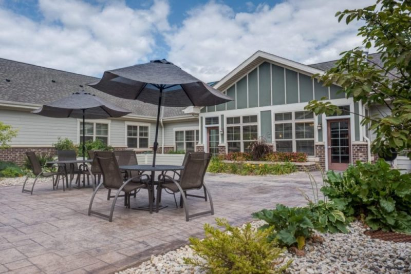 The outdoor patio with tables, chairs, and umbrellas at Heritage Court Waukesha.