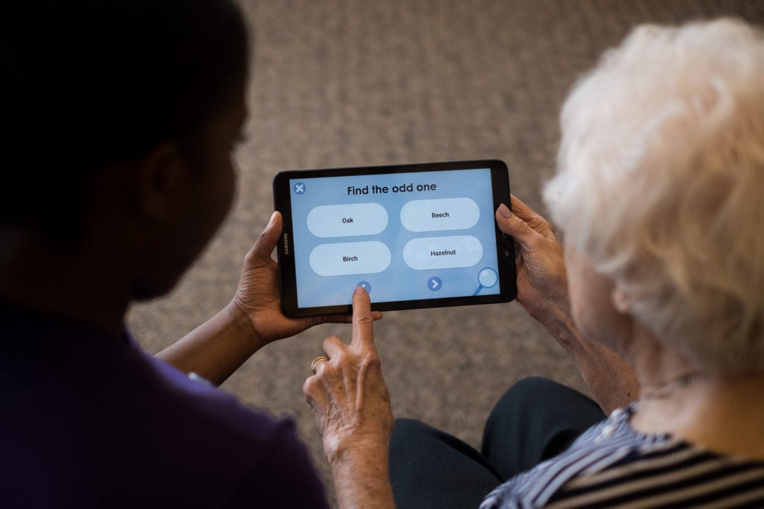 Two women work on a tablet for memory care activities.