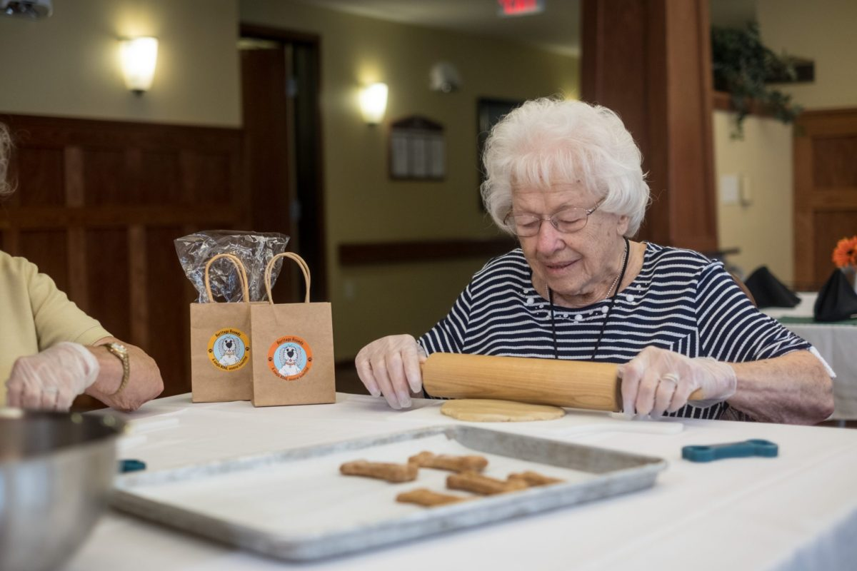 Woman uses a rolling pin to spread out cookie dough for treats during a group activity.