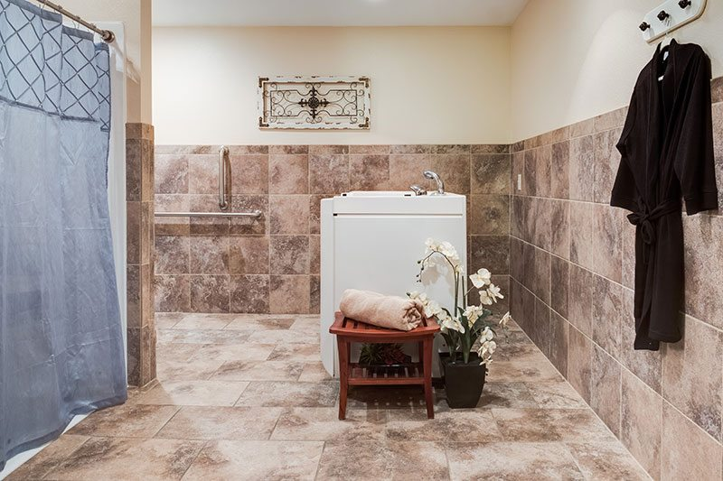 The spa rooms with tub, walk-in shower, and robe hanging at Heritage Waukesha.