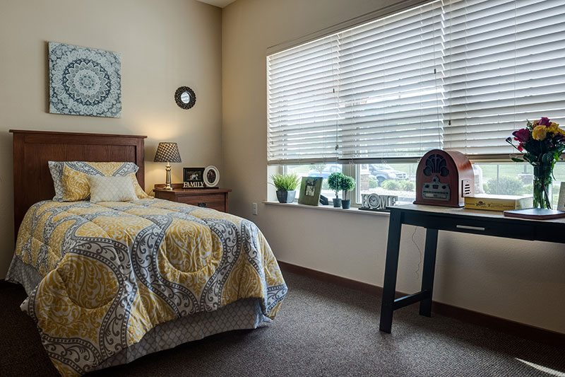 A memory care apartment with bed, nightstand, and desk.