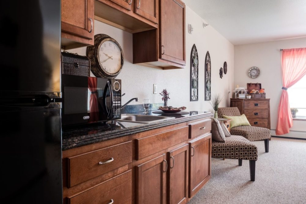 Kitchenette and living room in one of our assisted living apartments at Heritage West Allis.