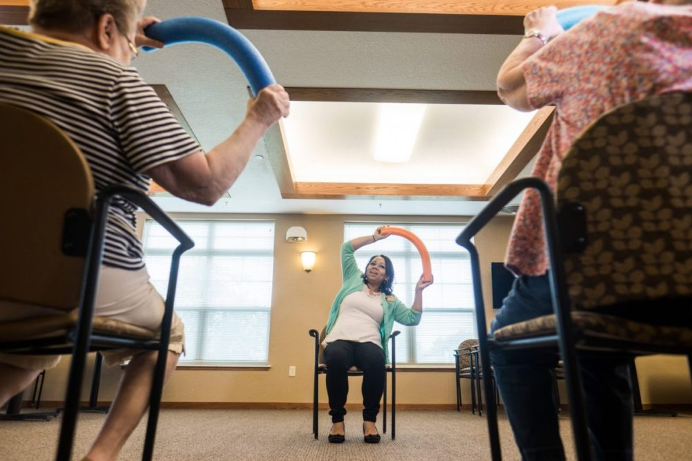 Woman leads class of seniors in exercise with a pool noodle.