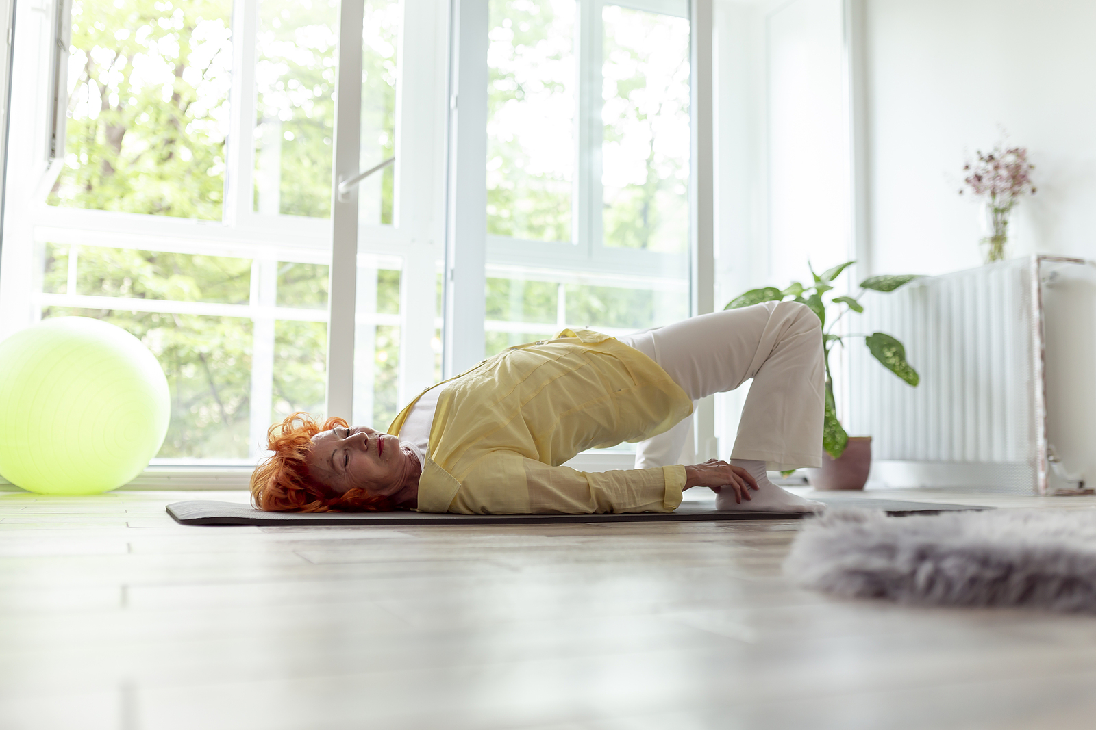 Senior woman completing a bridge pose, a lower back pain exercise.