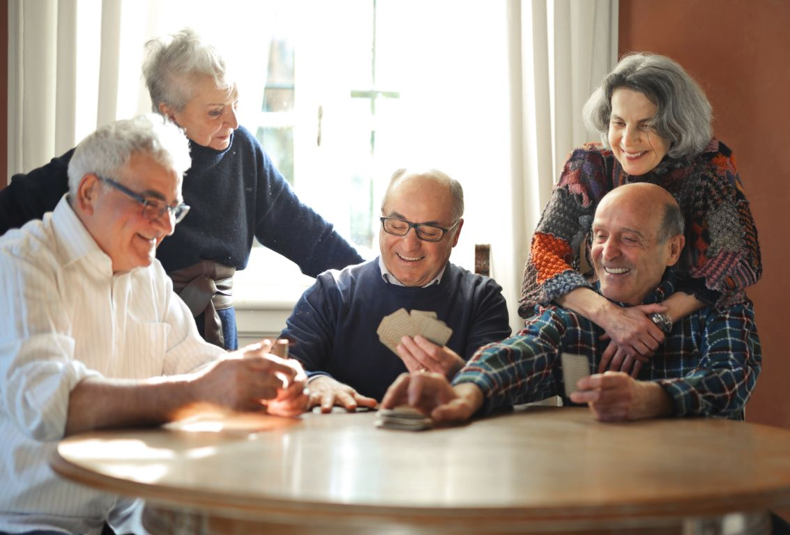 Seniors playing cards as part of their senior living activity program.