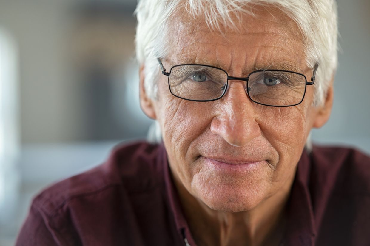 Senior man exhibiting signs of the normal aging process, including wrinkles in the skin, a need for corrective lenses and white hair.