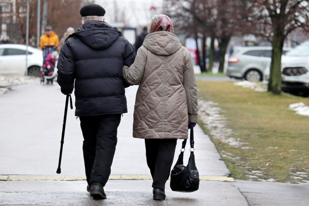 A senior couple walking, one with an assistive mobility device.