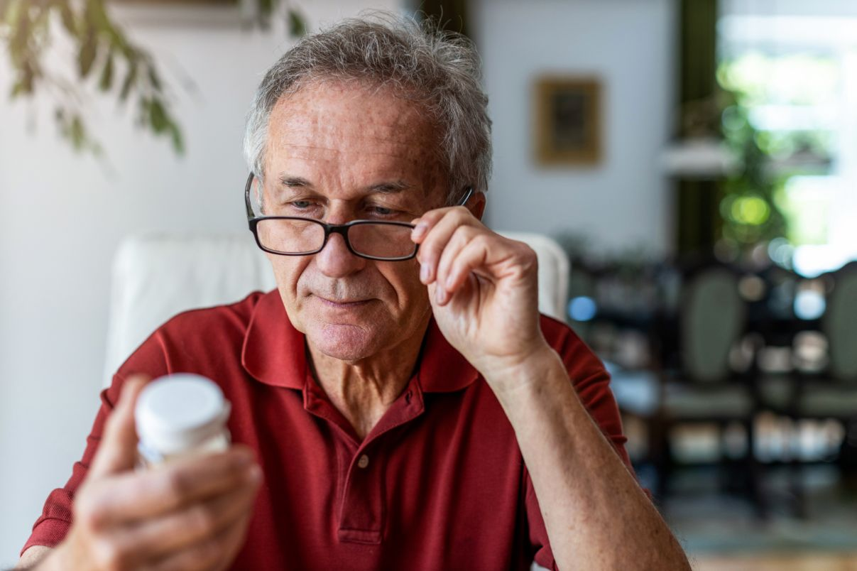Senior male reading drug interactions as a way to manage his medication.