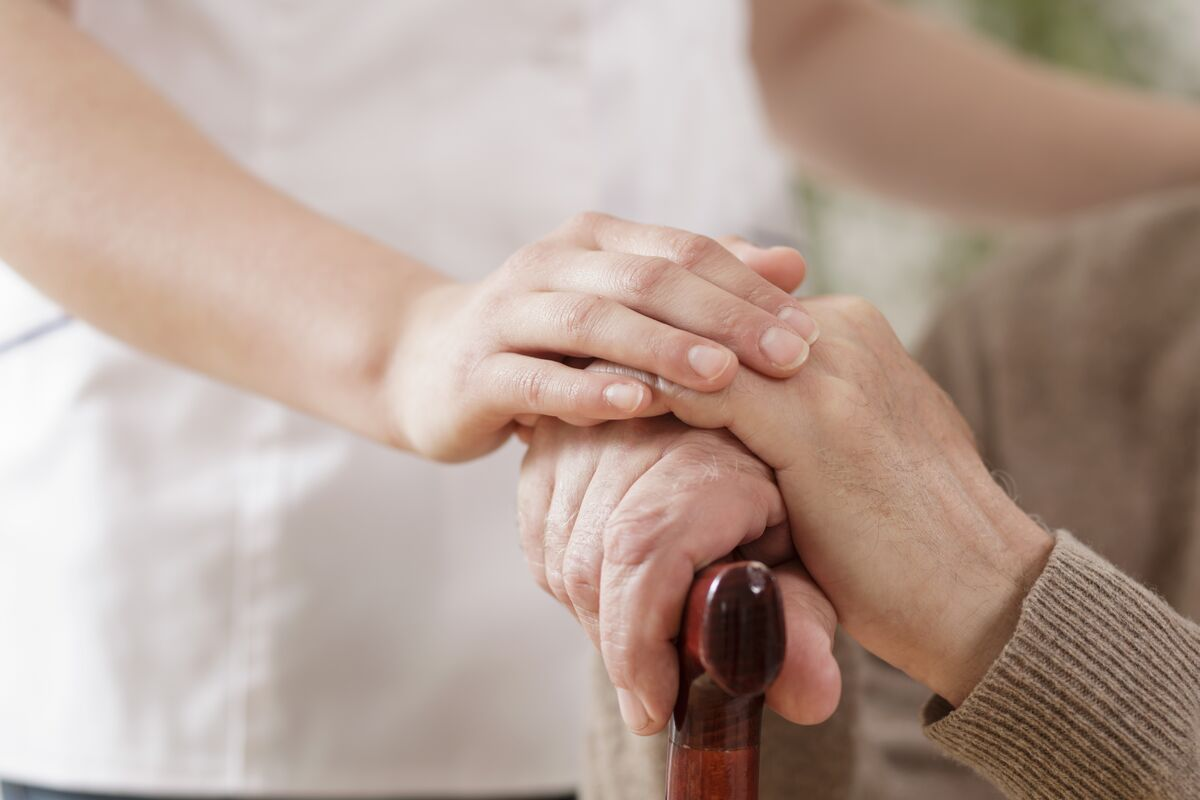 Young woman holding hands of senior man
