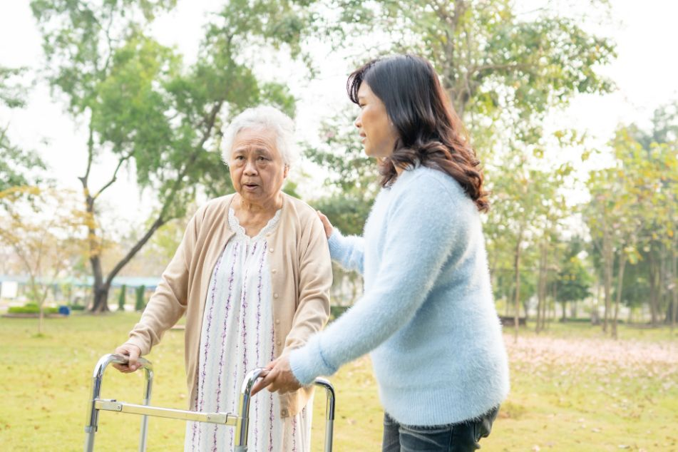 Senior experiences frailty using a walker to get around outside.