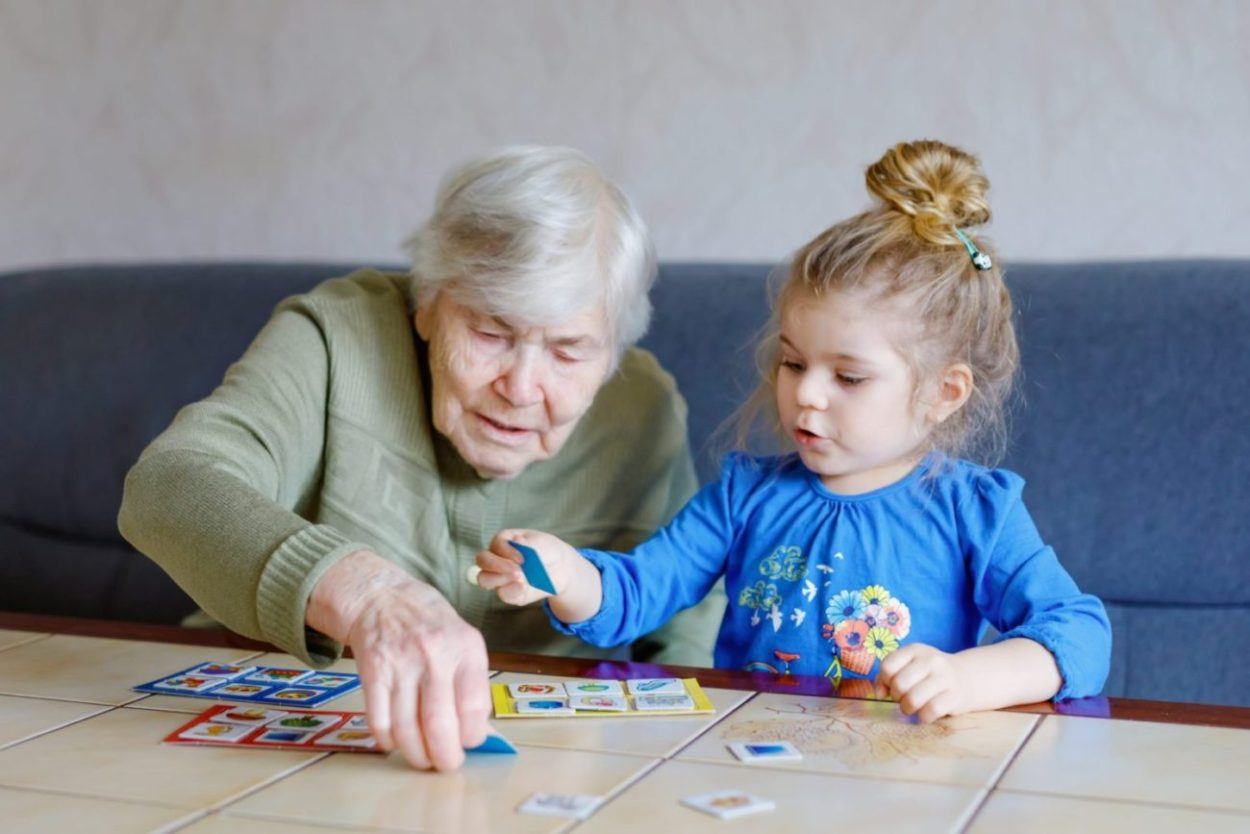 Senior woman with memory difficulties playing with grandchild.
