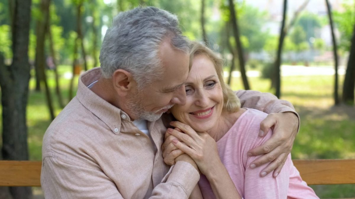 Senior couple embracing as they focus on their emotional wellbeing.