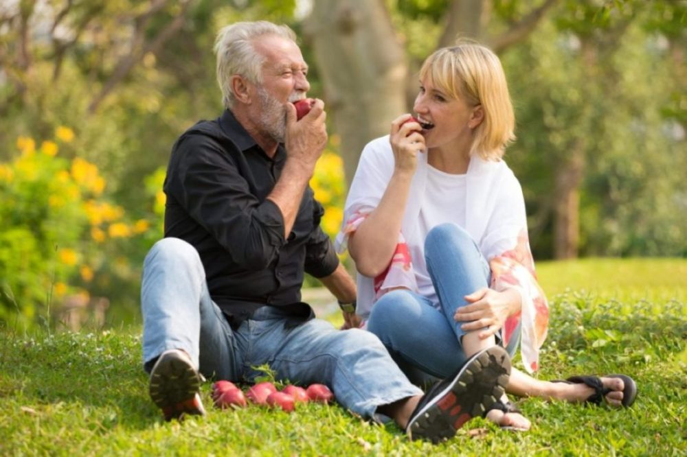 Senior couple enjoying summer foods during a picnic in the park.
